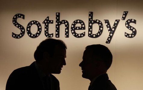Two men chat in front of a polka dot covered Sotheby's signage, part of an installation by Japanese artist Yayoi Kusama, at Sotheby's newly