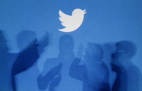 The shadows of people holding mobile phones are cast onto a backdrop projected with the Twitter logo in this illustration picture taken in W