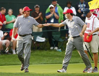 U.S. teammates Phil Mickelson (L) and Keegan Bradley bump fists after winning the 11th hole against International teammates Jason Day of Aus