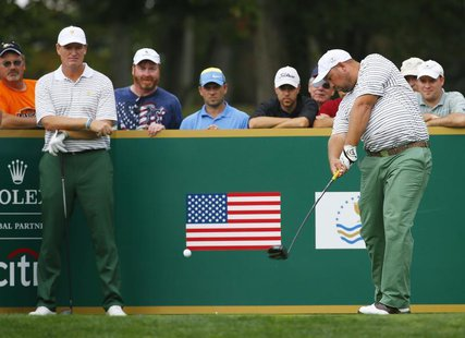 International team member Brendon de Jonge of Zimbabwe (R) is watched by teammate Ernie Els of South Africa as he tees off the ninth hole du