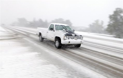 A pickup drives on Highway 44 as heavy snow falls in Rapid City, South Dakota, October 4, 2013. REUTERS/Chris Huber/Rapid City Journal