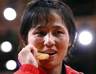 North Korea's An Kum Ae bites her gold medal as she celebrates during the awards ceremony for the women's -52kg judo competition at the Lond