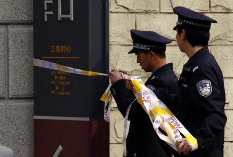 Policemen remove tape from the entrance to the courthouse where disabled lawyer Ni Yulan, and her husband Dong Jiqin were being sentenced, i