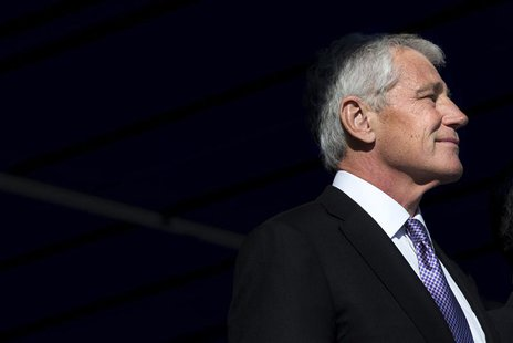 U.S. Secretary of Defense Chuck Hagel, illuminated by a beam of sunlight, attends a change of command ceremony, that sees U.S. Army General