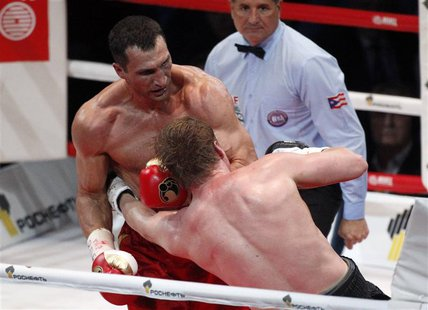 Heavyweight world champion Vladimir Klitschko (L) of Ukraine and challenger Alexander Povetkin of Russia exchange punches during their heavy