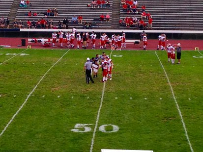 The captains for the Coldwater Cardinals and Loy Norrix Knights meet at midfield for the coin toss before their October 4, 2013 game.