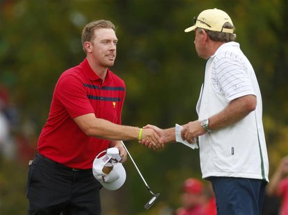 Hunter Mahan of the U.S. (L) shakes hands with International team captain Nick Price of Zimbabwe after he and Brandon Snedeker defeated Inte