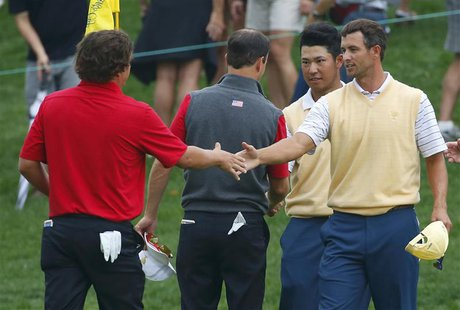 Jason Dufner (L) of the U.S. shakes hands with Adam Scott (R) of Australia as Zach Johnson of the U.S. shakes hands with Hideki Matsuyama of