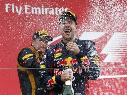 Second placed Lotus Formula One driver Kimi Raikkonen of Finland (L) sprays champagne at winner Red Bull Formula One driver Sebastian Vettel
