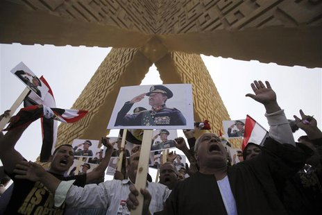 Supporters of the army hold posters of late Egyptian President Anwar Sadat as they protest against ousted Islamist President Mohamed Mursi a