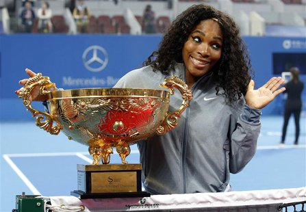 Serena Williams of the U.S. reacts as she poses with the trophy after winning her women's singles final match against Jelena Jankovic of Ser