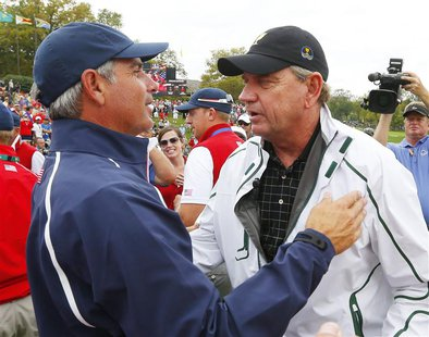 International captain Nick Price (R) congratulates U.S. captain Fred Couples after the U.S. won the 2013 Presidents Cup golf tournament at M