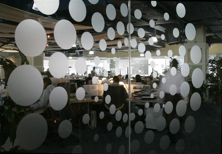 The new Thomson Reuters logo is seen as employees sit at their desks in the Dubai office April 17, 2008. REUTERS/Jumana El Heloueh