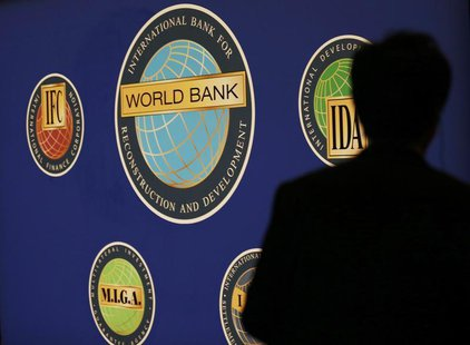 A man is silhouetted against the logo of the World Bank at the main venue for the International Monetary Fund (IMF) and World Bank annual me