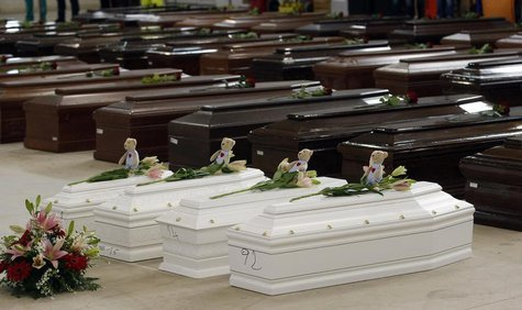Coffins (in white) of children are seen alongside coffins of other victims from a shipwreck off Sicily, in a hangar of the Lampedusa airport