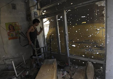 A Free Syrian Army fighter carries his weapon as he peeks out from a damaged shop in Deir al-Zor October 6, 2013. Picture taken October 6, 2