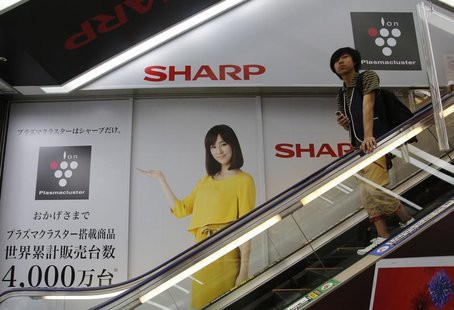 A man rides an escalator past Japanese display maker Sharp Corp's advertisements at an electronics retail store in Tokyo May 14, 2013. REUTE