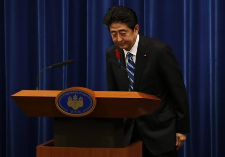 Japan's Prime Minister Shinzo Abe bows at the end of a news conference to announce a raise in the sales tax rate at his official residence i