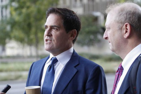 Mark Cuban (L), the billionaire owner of the NBA's Dallas Mavericks, speaks with the media while his attorney Stephen Best (R) looks on prio
