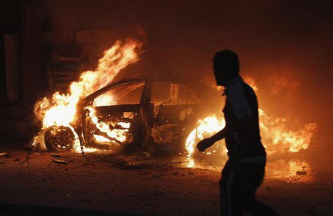 A man looks at a car on fire at the site of a bomb attack in Baghdad October 7, 2013. REUTERS/Ahmed Saad