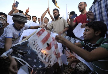 Protesters burn a replica of the U.S. flag during a protest against the capture of Nazih al-Ragye, in Benghazi October 7, 2013. REUTERS/Esam