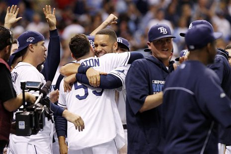 Oct 7, 2013; St. Petersburg, FL, USA; Tampa Bay Rays catcher Jose Lobaton (59) is congratulated by first baseman James Loney (middle, facing