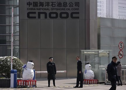 Security personnel stand next to snowmen at the entrance of China National Offshore Oil Corp (CNOOC) office tower in Beijing, March 20, 2013