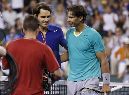 Roger Federer of Switzerland and Rafael Nadal (R) of Spain greet each other at the net after Nadal defeated Federer in their men's singles q