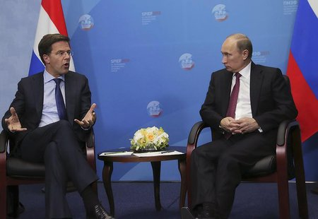 Russia's President Vladimir Putin (R) speaks with Netherlands' Prime Minister Mark Rutte during their meeting at the International Economic