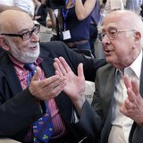 File picture of British physicist Peter Higgs (R) talking with Belgium physicist Francois Englert before a news conference on the search for