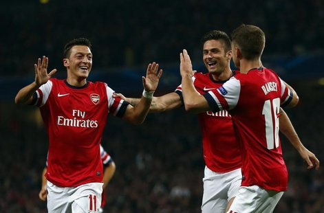 Arsenal's Mesut Ozil (L) celebrates with teammates Olivier Giroud and Aaron Ramsey (R) after scoring a goal against Napoli during their Cham
