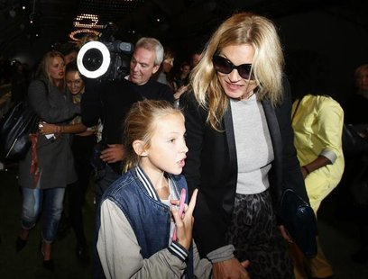 British model Kate Moss leaves the Topshop Unique Spring/Summer 2014 collection with her daughter Lila Grace during London Fashion Week Sept