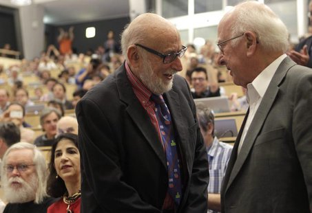 British physicist Peter Higgs (R) shakes hands with Belgium physicist Francois Englert before a scientific seminar to deliver the latest upd