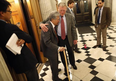 U.S. Senator James Inhofe (R-OK) (C) hugs Senator Daniel Akaka (D-HI) (center L) as they cross paths during a senate vote in the early morni