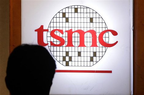A man sits in front of the logo of Taiwan Semiconductor Manufacturing Co Ltd (TSMC) during an investors' conference in Taipei in this April