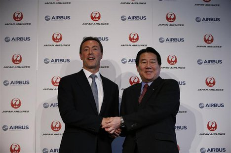 Japan Airlines President Yoshiharu Ueki (R) shakes hands with Airbus Chief Executive Fabrice Bregier during their joint news conference in T