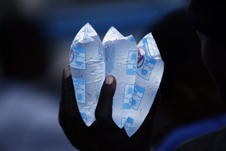 A resident holds packets of water to sell in downtown Port-au-Prince November 23, 2010. REUTERS/ Eduardo Munoz