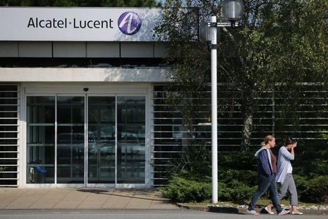 Employees of Alcatel-Lucent walk past an entrance at the company site in Orvault near Nantes, western France, October 8, 2013. REUTERS/Steph