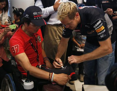 Red Bull Formula One driver Sebastian Vettel of Germany signs his autograph for a fan after speaking at an event at Nissan Motor Co's global