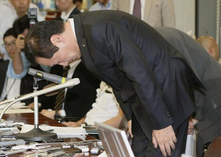 Mizuho Financial Group President Yasuhiro Sato bows during a news conference at the Bank of Japan headquarters in Tokyo, in this photo taken