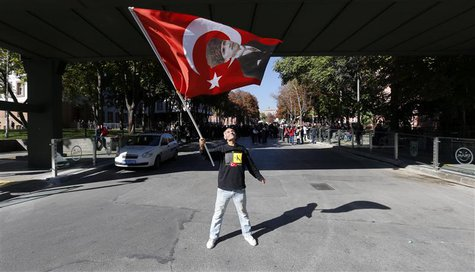 A protester waves a Turkish flag printed with a portrait of Mustafa Kemal Ataturk, the founder of modern Turkey, on a road which leads to a