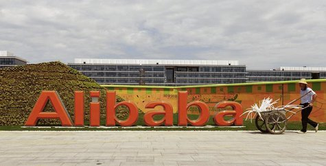 A worker walks past a logo of Alibaba Group at its headquarters on the outskirts of Hangzhou, Zhejiang province, August 24, 2013. REUTERS/Ch