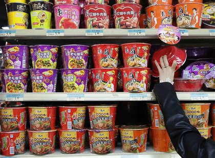 A woman chooses a cup noodle from a shelf displaying cup noodles from Uni-President China (top and middle) and Tingyi (bottom) at a supermar