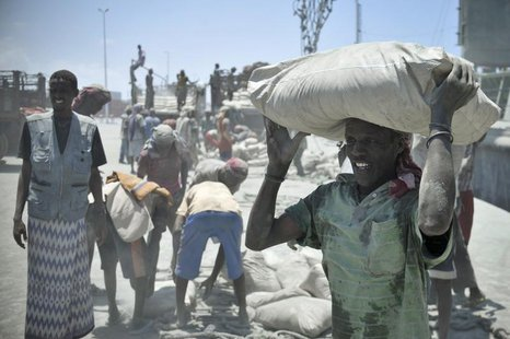 A Somali man carries a bag of cement on his head, after it was unloaded from a ship, at Mogadishu's main port April 15, 2013. REUTERS/Tobin