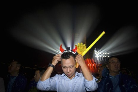 Jonathan Lu, new chief executive of Alibaba Group, puts on a headband with horns during the celebration of the 10th anniversary of Taobao Ma