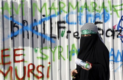 A pro-Palestinian demonstrator stands next to graffiti during an anti-Israeli protest outside the Justice Palace in Istanbul October 10, 201