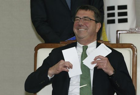 U.S. Deputy Secretary of Defence Ashton Carter holds letters before talks with South Korean Defence Minister Kim Kwan-jin (not pictured) at