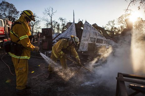 Shasta County firefighters Zach Lacy (L) and Bob Baker spray water on a home burnt by the Clover Fire in Happy Valley, California September
