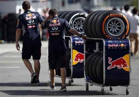Red Bull Formula One team members move Pirelli tires near the pits at the Suzuka circuit in Suzuka October 10, 2013, ahead of Sunday's Japan