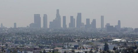 The skyline of downtown Los Angeles through a layer of smog is seen in the distance from a rooftop in Hollywood, California, May 31, 2006. R